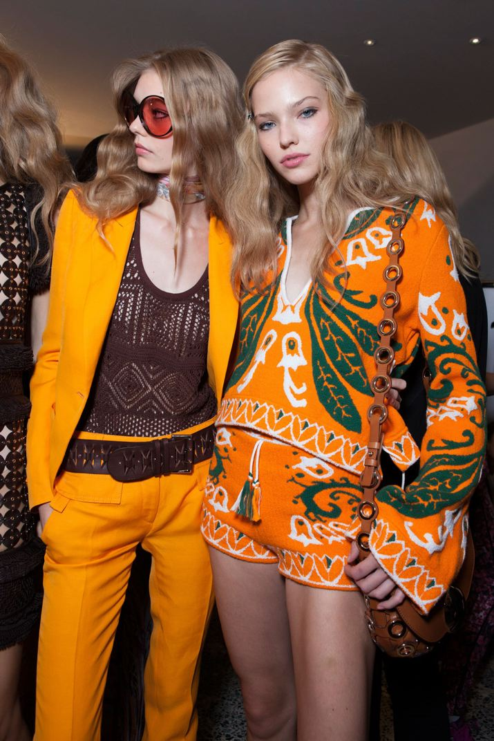 Two models wearing orange groovy spring trends